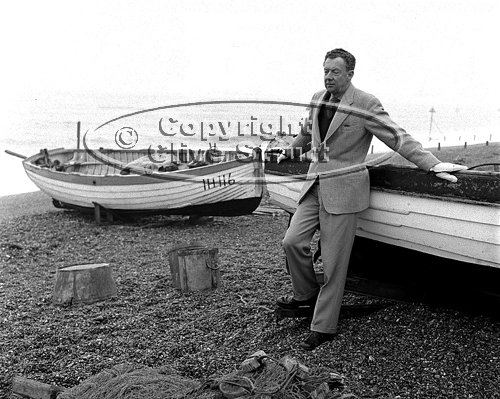 Benjamin Britten leaning on boat at Aldeburgh beach