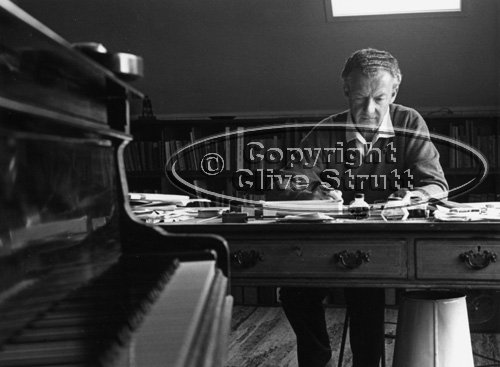 Benjamin Britten working at his desk with piano