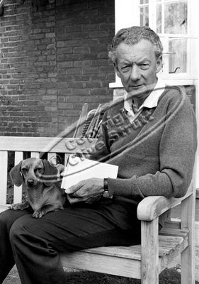 Benjamin Britten sitting on garden seat with dog