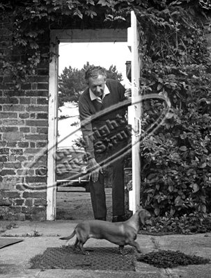 Benjamin Britten with his dog in garden archway