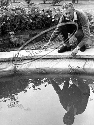Benjamin Britten with dog beside garden pond