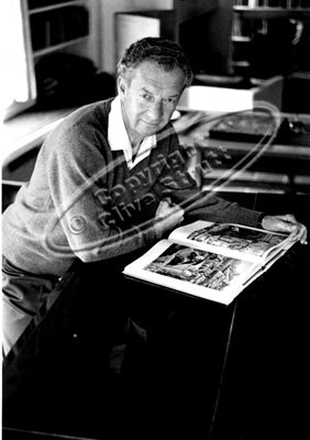 Benjamin Britten leaning on piano with book