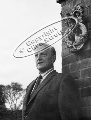Peter Pears standing by wall statue at Red House